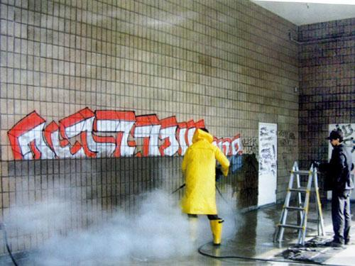 Workers cleaning graffiti off the side of a building