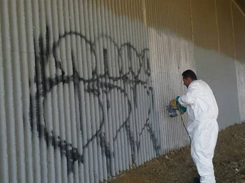 Worker cleaning graffiti off the side of a building