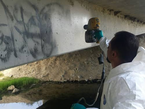 Worker cleaning graffiti off the underside of a bridge